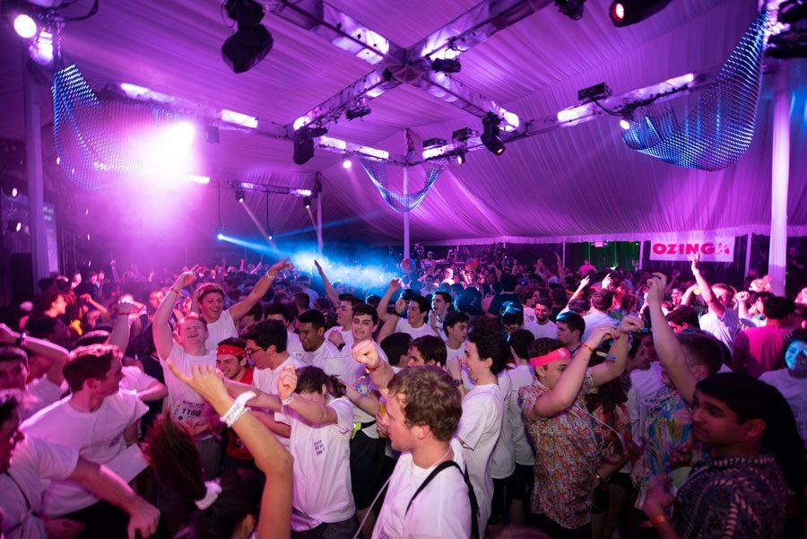 Students dance under a white tent during Dance Marathon 2019. There are purple strobe lights and most students wear white t-shirts while waving their arms in excitement as they dance.