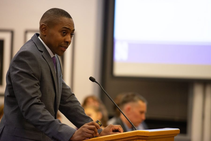 A Black man stands speaking in front of a podium in a grey suit with a purple tie.
