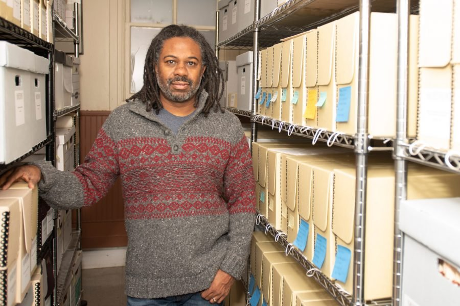 Shorefront Legacy Center founder Dino Robinson stands between two shelves, filled with boxes of archival documents.
