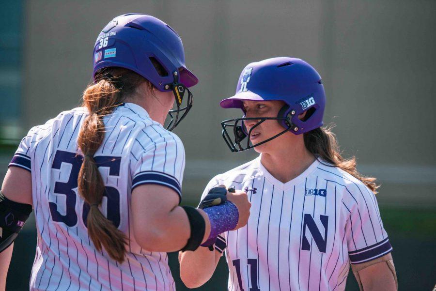 Northwestern softball players with purple batting helmets talking