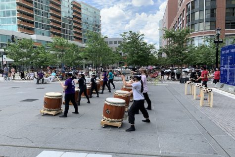 Drummers play their drums in the middle of a city square. There are two rows of drummers in front with larger brown drums, and one row of drummers in the back with smaller drums.