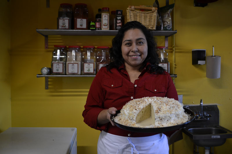 Tania+Merlos-Ruiz+poses+with+a+white+cake.+She+is+wearing+a+red+shirt+and+stands+in+front+of+a+yellow+wall.