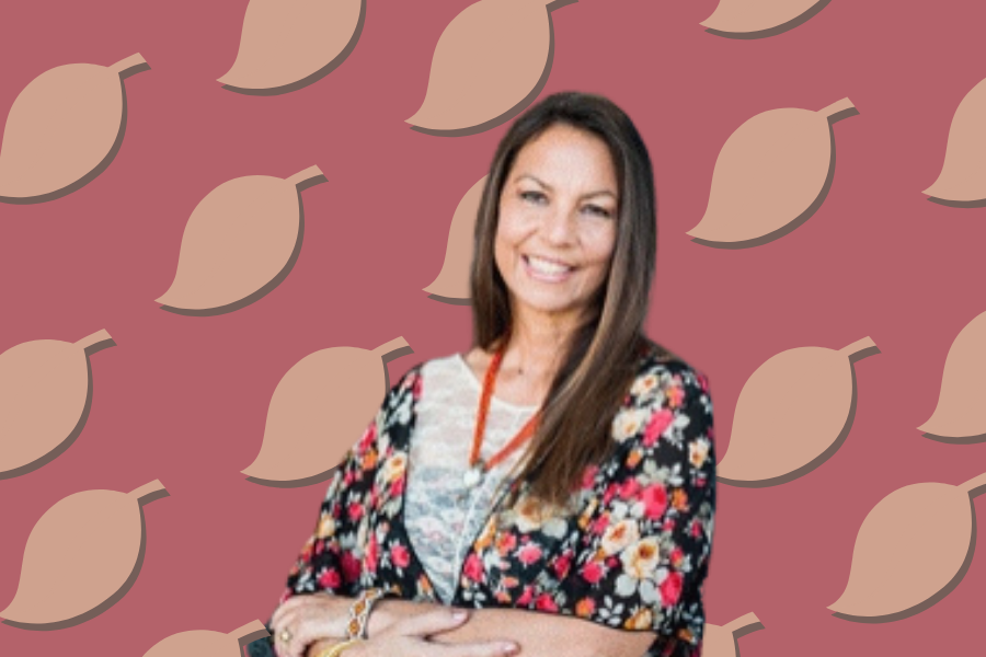 Dina Gilio-Whitaker is wearing a pink, white and black floral cardigan over a white shirt. The background is pink with tan and brown leaves.