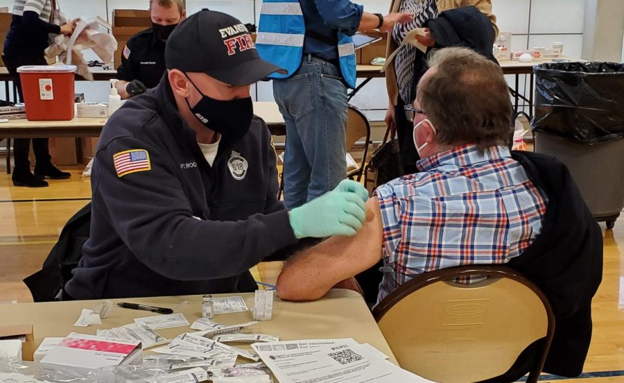 A volunteer health worker and firefighter, dressed in black administers a bandage to a man with a checkered shirt and glasses, both wearing masks. Tables are set up in the background.
