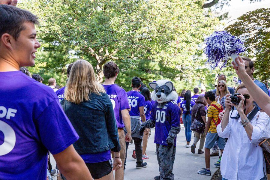 A line of students in purple shirts walk along a grey path. The path is lined with green trees, and to the side parents stand cheering and taking pictures.