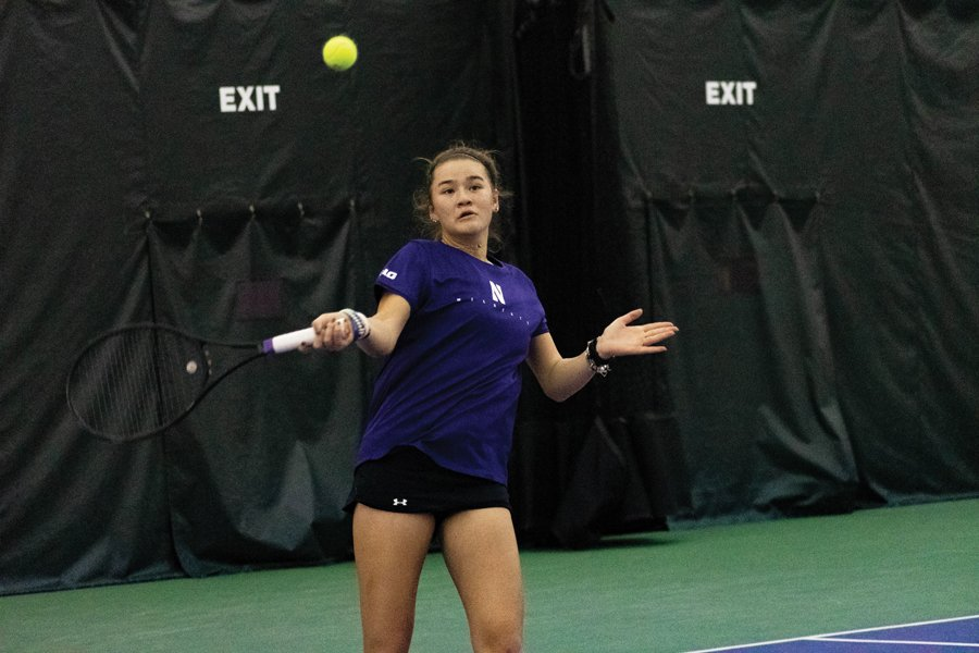 Girl in purple uniform hits the ball with black stick on the green tennis court.