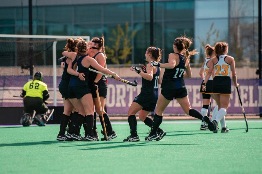 Girls in black uniforms all hug each other on the green field