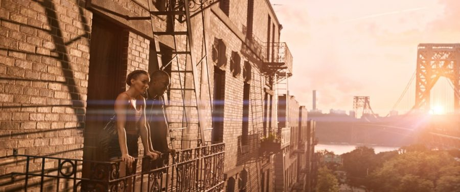 A man and a woman lean on the railing of a porch of an apartment, looking out into the city at sunset. There is a bridge in the background.