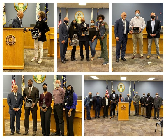 Five photos of outgoing Mayor Steve Hagerty with the recipients of the Keys to the City award. In the top left, Hagerty is shaking hands with someone in a black jacket holding an award with the key on it. The other four photos are the recipients posing in a room with a blue wall, brown podium and gray floor.