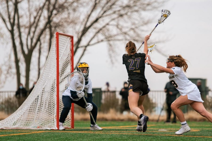 A lacrosse player wearing black holding a stick shoots a ball on goal.