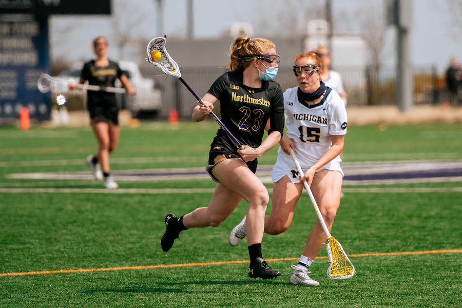A+lacrosse+player+wearing+black+runs+down+the+green+field+with+the+ball%2C+followed+by+one+defender+wearing+white.