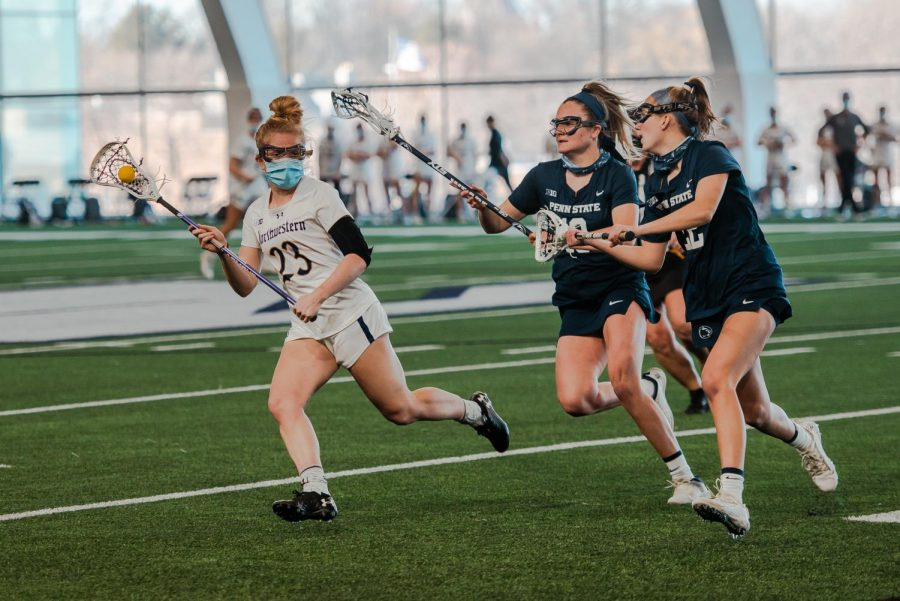 A lacrosse player wearing white runs down the green field with the ball, followed by two defenders wearing blue.