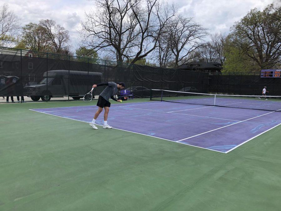 Men's tennis player holding ball prepares to serve.