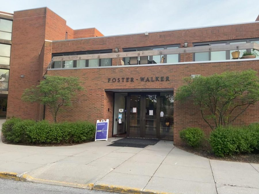 """The Foster-Walker Complex building. The bricks are brown with green shrubbery on both sides of the main door. Above the door are the words """"Foster-Walker."""""""