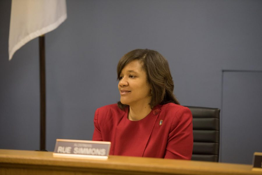 Robin Rue Simmons sits at her desk at a city council meeting. Her desk is brown, the chair is black, her shirt is red, and the background is light blue.
