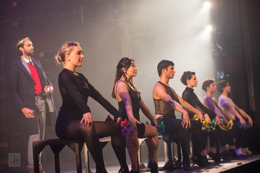 A row of six performers on stage face forward, off camera. Behind them, a man looks out as well.