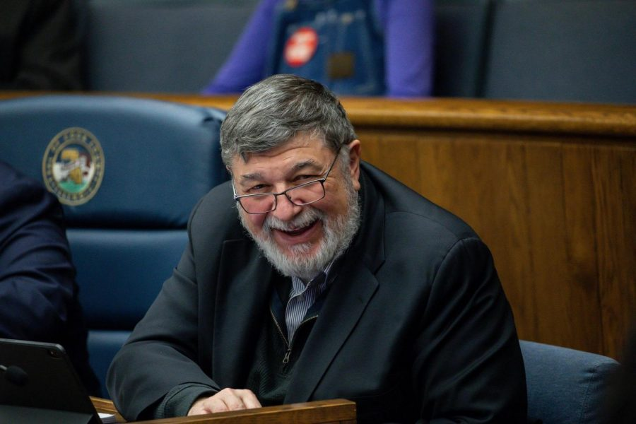 Larry Suffredin sits in a blue chair and is wearing a black suit jacket and glasses. He appears to be laughing.