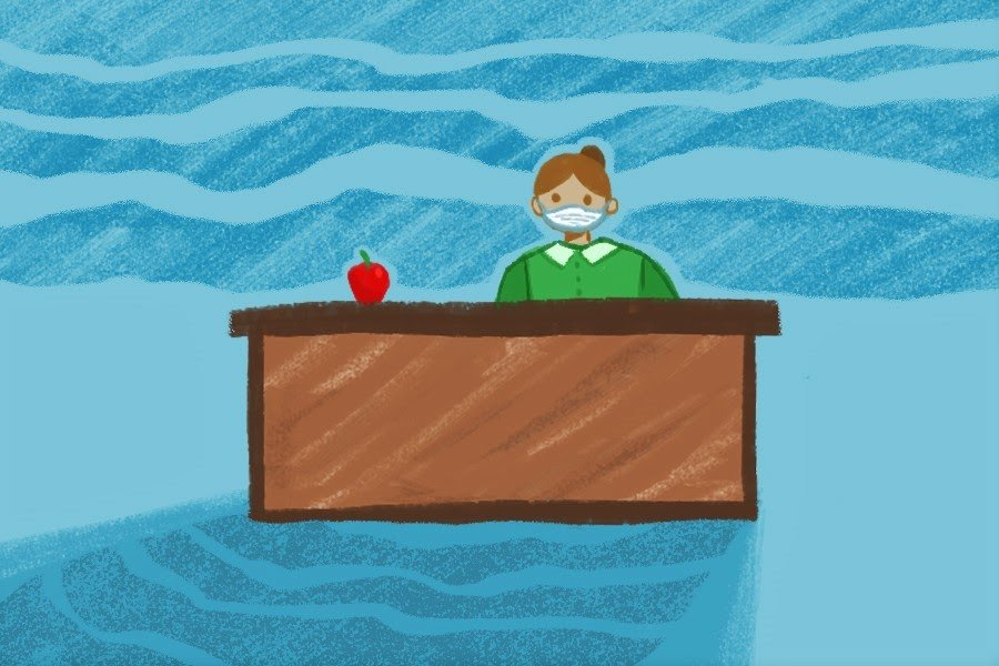 Girl in green shirt sitting at desk with a red apple