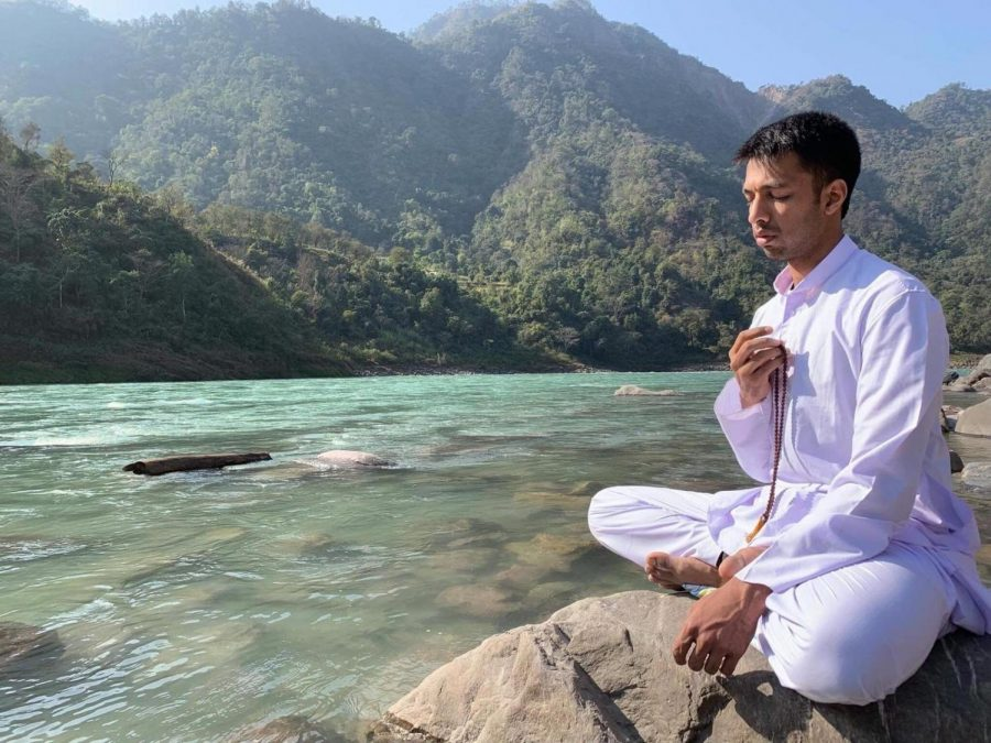 Amar Shah is meditating alongside an aqua river and green mountains. He is barefoot and wears all white clothing.