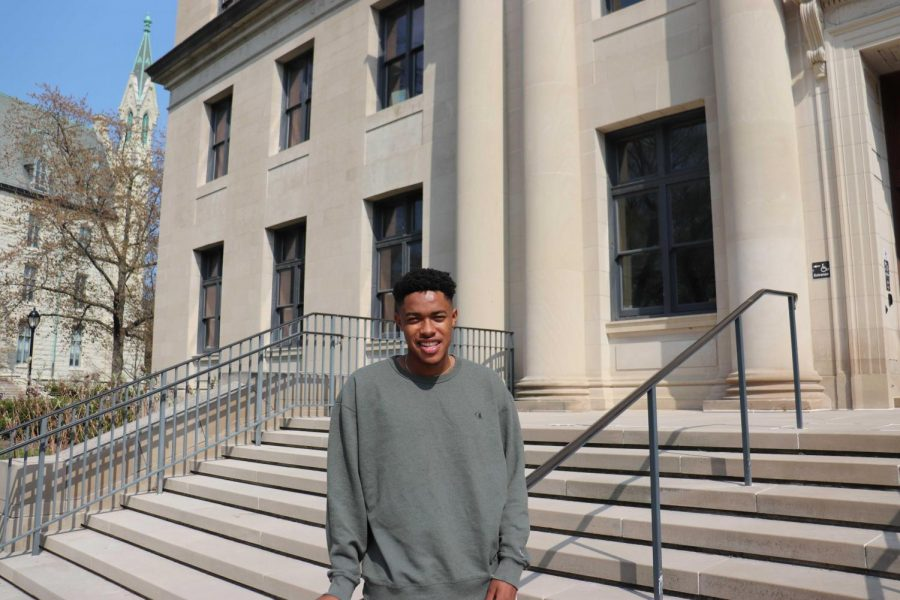 Christian Wade. He is wearing a gray sweatshirt. In the background is a tan campus building with stairs in the front and bare trees in the back.