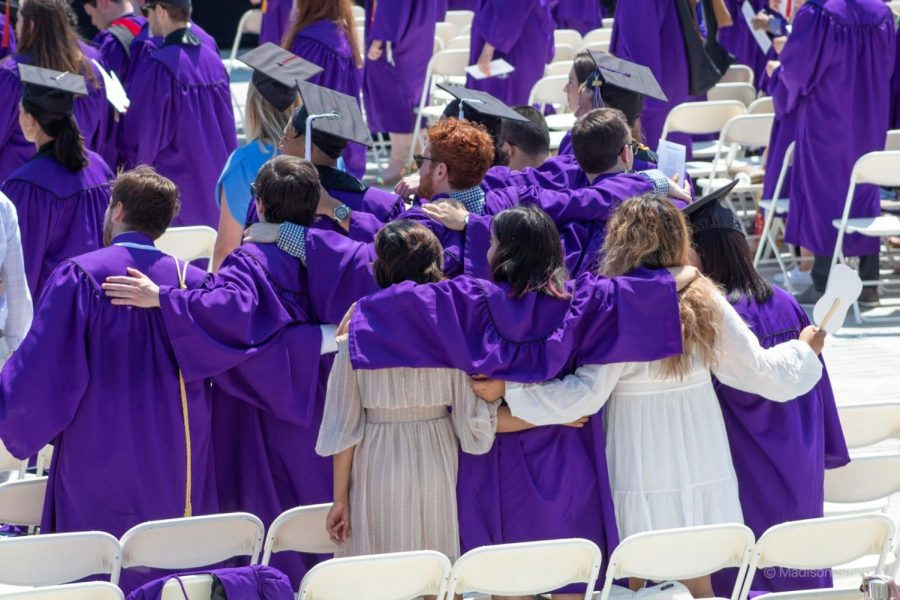 Group of people in graduation attire face away from the camera and hold each other's shoulders while standing in front of folding chairs.