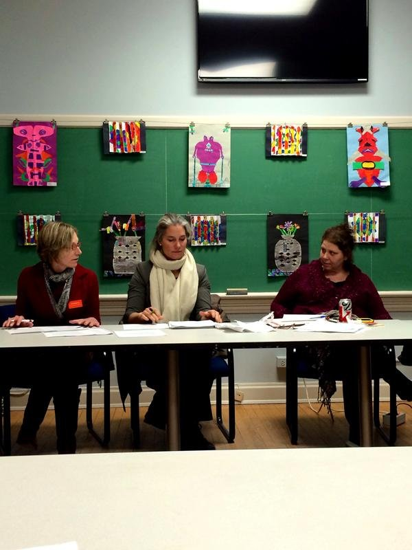 Three middle-aged women sit at a table during a meeting. There are papers strewn across the table, and art decorates the wall behind them.