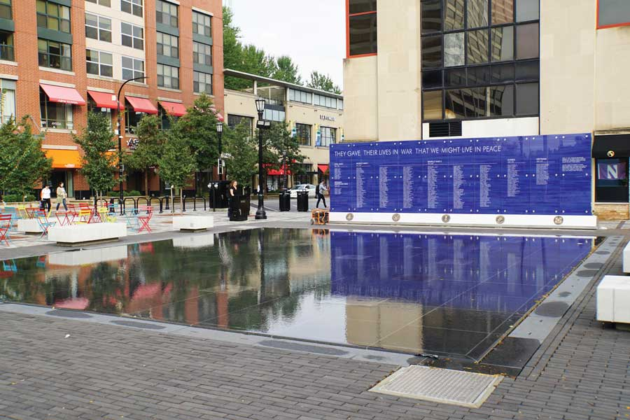 A gray fountain in front of a blue memorial wall, surrounded by outdoor seating.