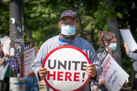 """A man looking into a camera. He is wearing a grey smock and is holding a circular white sign reading """"Unite Here!"""""""