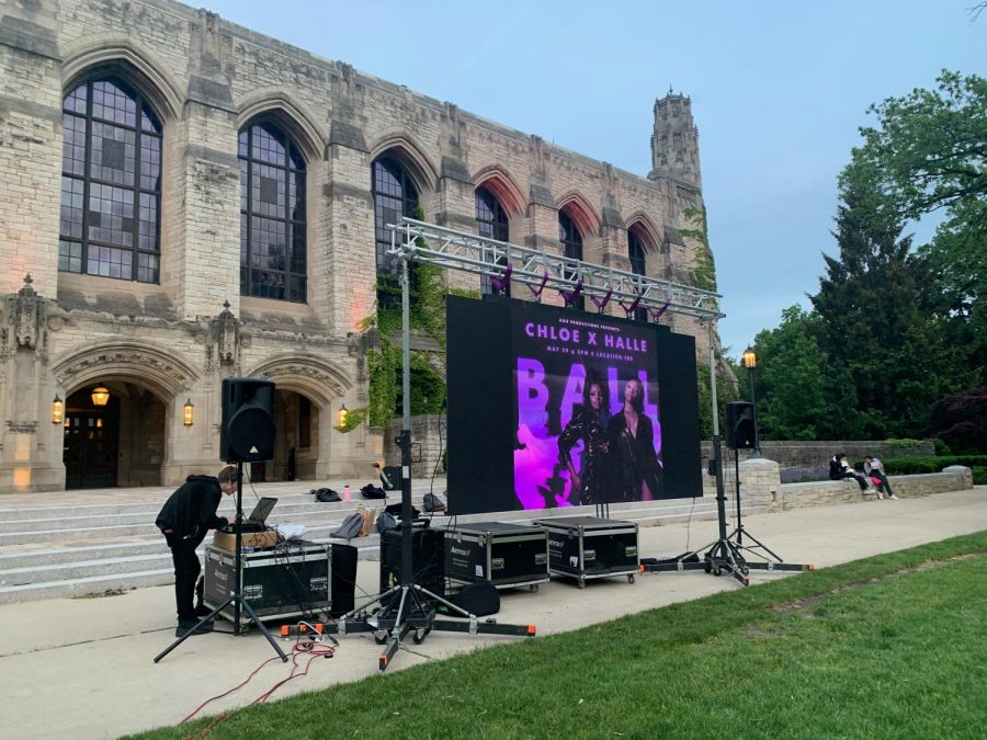 """Deering Library, a tan building, on the left. On the right is green grass. In the middle is a screen set up with a purple and black image. Words """"CHLOE X HALLE"""" are visible."""