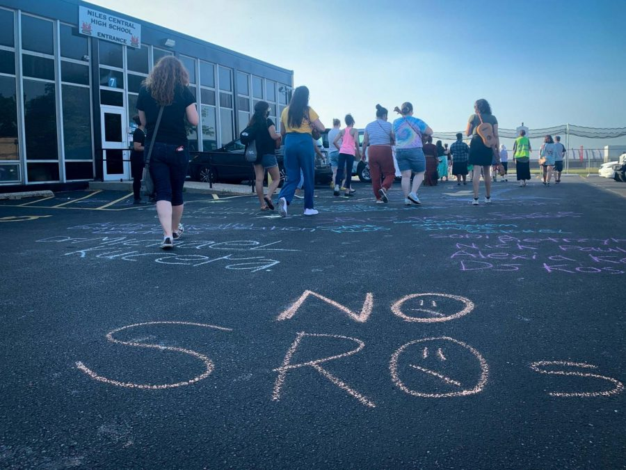 """""""No SROs"""" written in orange chalk on pavement outside a medium one-story building. Many people are walking around toward the back of the building, facing away from the camera and stepping over more chalk messages."""