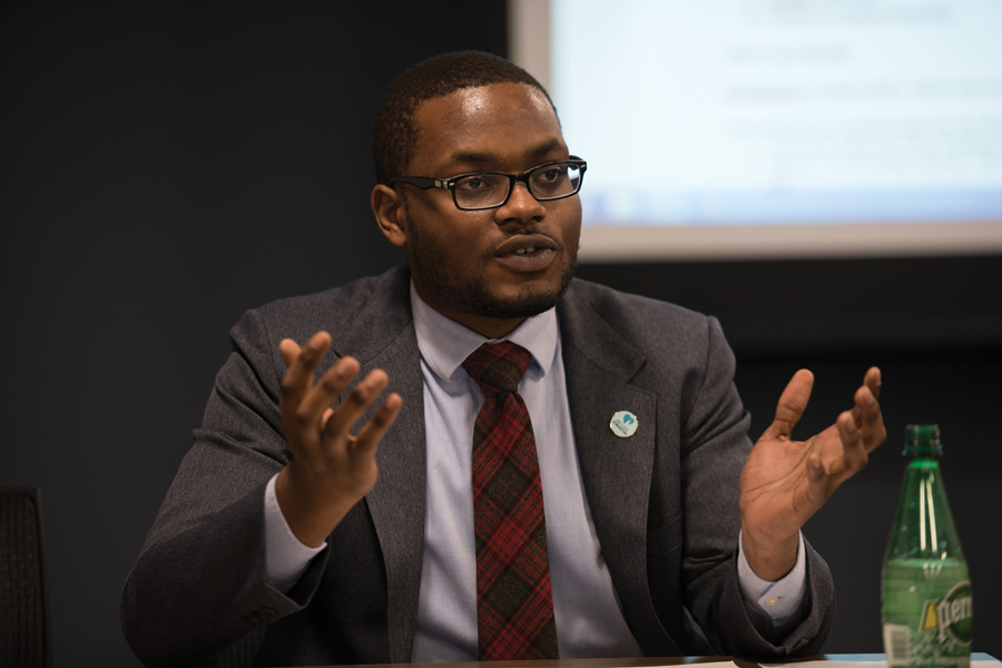 Ald. Devon Reid (8th), a Black man, sits wearing a black suit with a red tie and a white lapel pin. There is a projector screen in the background and a green plastic drink bottle next to him.