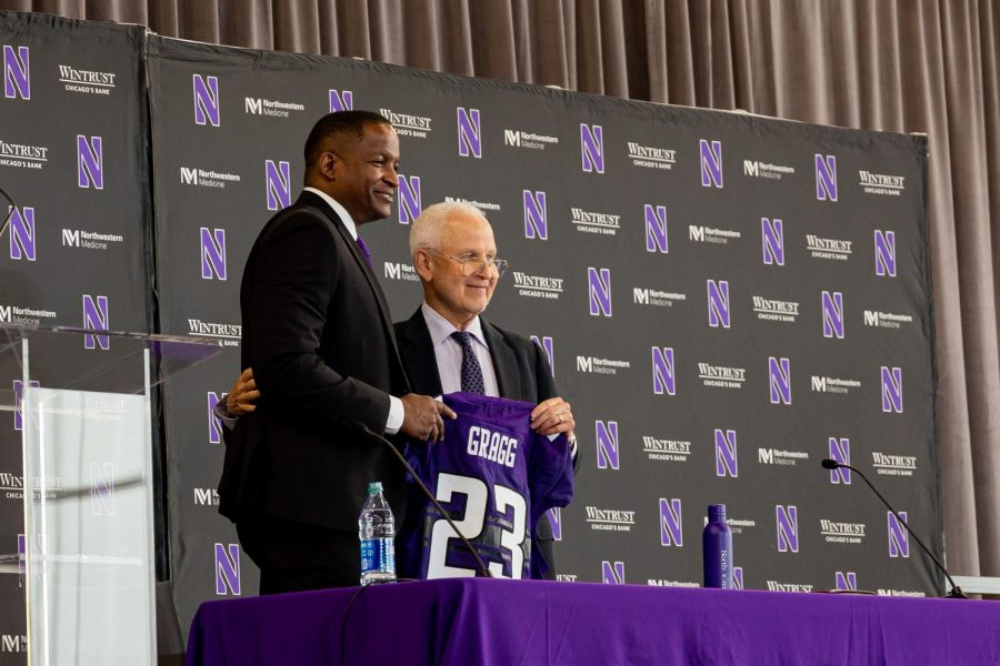 Two men in suits hold a purple jersey with No. 23 and the name Gragg on it, standing in front of a black poster with the Northwestern logo and the words Wintrust.