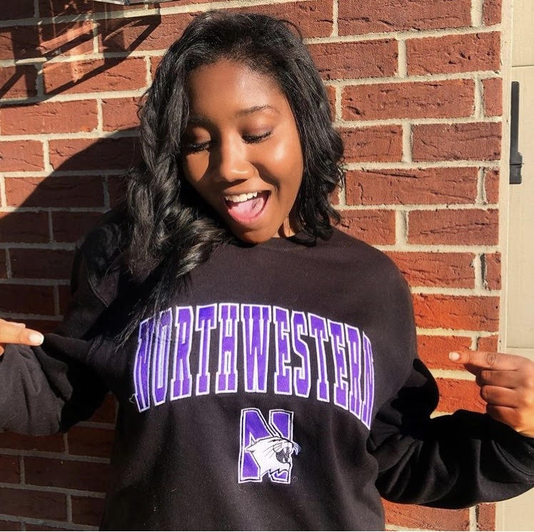 Simone Scott wears a gray sweatshirt with a Northwestern logo. In the background is a brown brick wall.