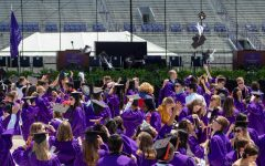 Crowd of people in purple graduation gowns gathered on a field, some throwing their caps into the air, with bleachers and a podium in the background.