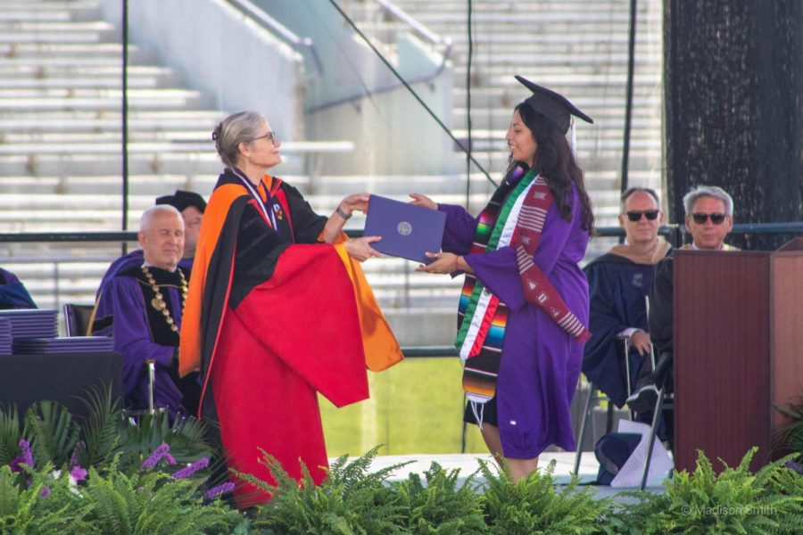 Provost Kathleen Hagerty presents a purple diploma to a member of the Class of 2020. Both are wearing graduation gowns and on a stage.