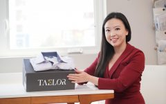 """Anya Cheng sits on the right side, wearing a burgundy suit. She holds a gray rectangular box with the words """"Taelor."""""""