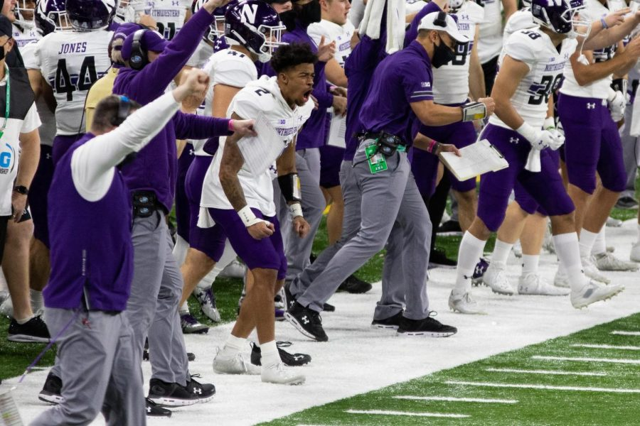 Individuals+in+purple+and+white+jerseys+and+purple+and+white+shirts+fist+pump+and+yell+in+celebration+on+green+and+white+turf+field.