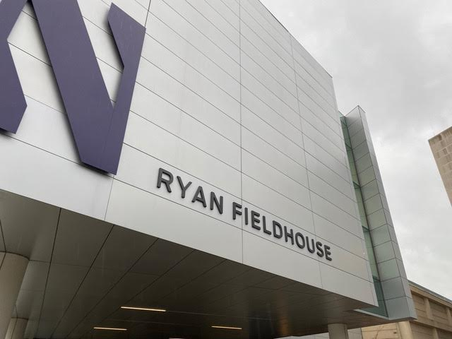 Gray building with metallic blocks and big purple N on the front.