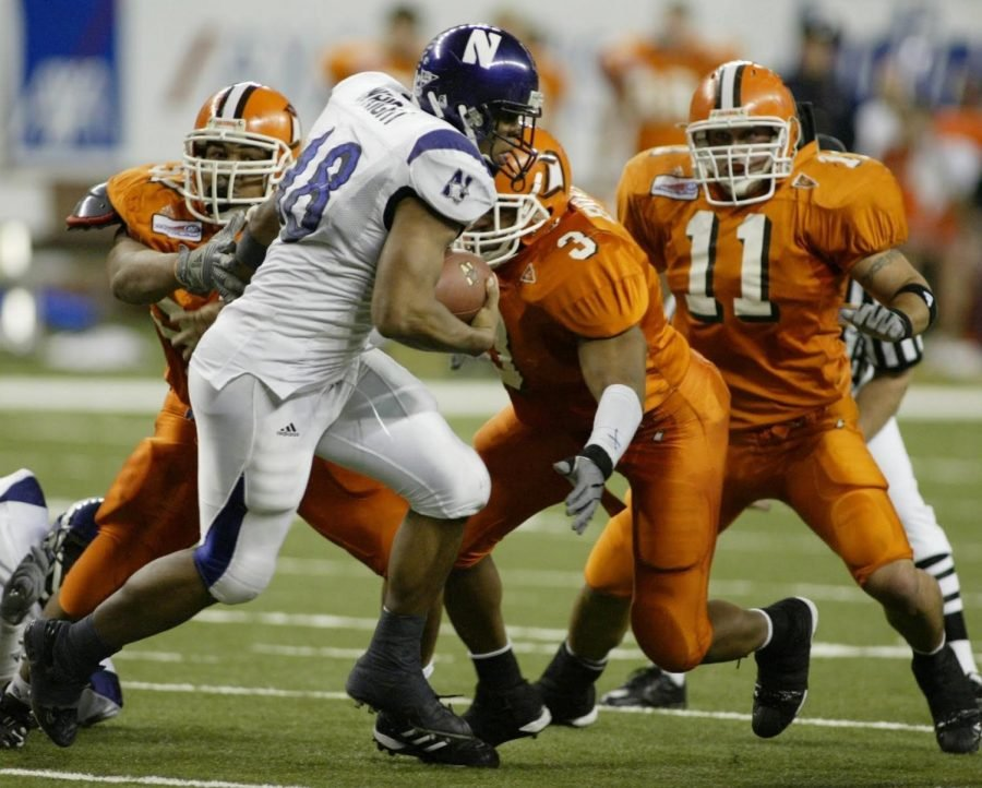 A running back carries the football against three defenders.