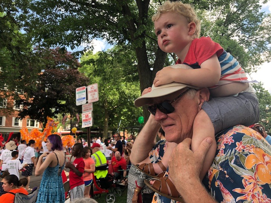 A white man in a floral shirt, black sunglasses, and a tan hat holds a young blond-haired boy on his shoulders with a colorful t-shirt and corduroy shorts. Parade onlookers cover the rest of the photo in the background.