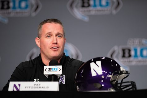 Coach Pat Fitzgerald looks out at a crowd, wearing a white polo and sitting in front of a microphone on a table.