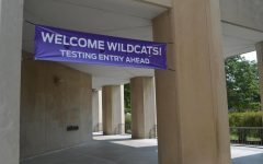 """A gray and tan walkway with five visible pillars. A purple banner reads: """"Welcome Wildcats! Testing Entry Ahead."""""""
