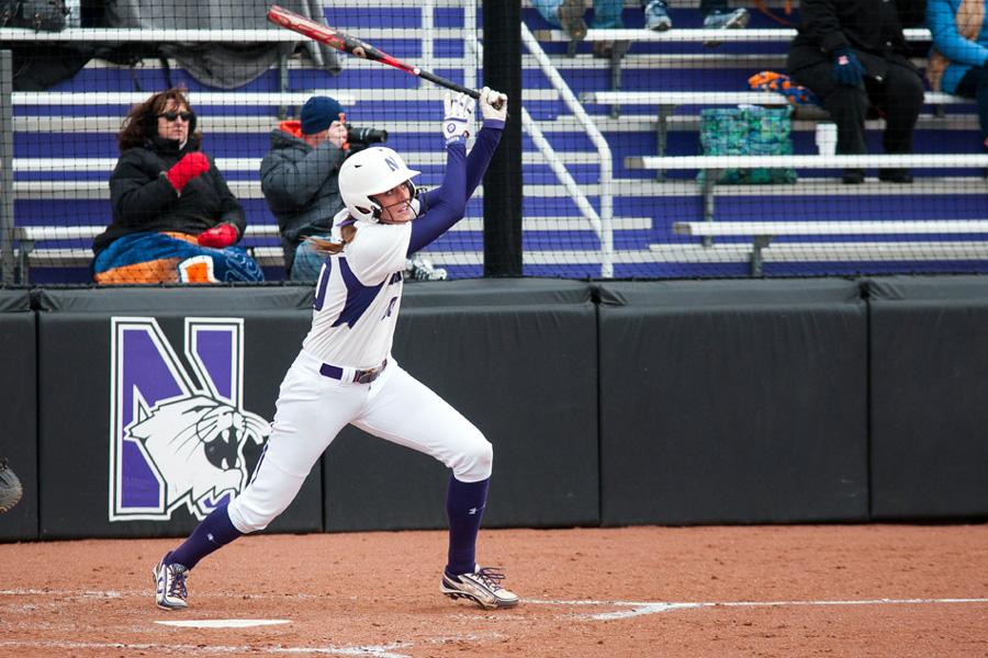 Northwestern softball player in white uniform holding bat stares at a fly ball.