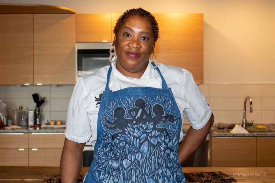 Chef Q. Ibraheem stands in a kitchen, wearing a blue apron and a white shirt.