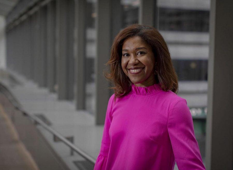 Prof. Inger Burnett-Zeigler smiles in front of glass windows wearing a bright pink shirt.
