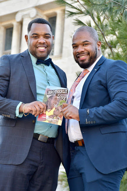 Gilbert and Michael Allen stand next to each other in suits holding a copy of their book,