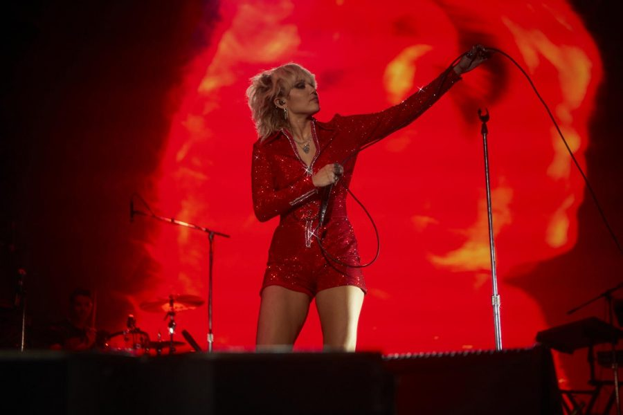 Miley Cyrus, wearing a red sequined jumpsuit, looks out into the crowd, arm extended, while holding her mic.