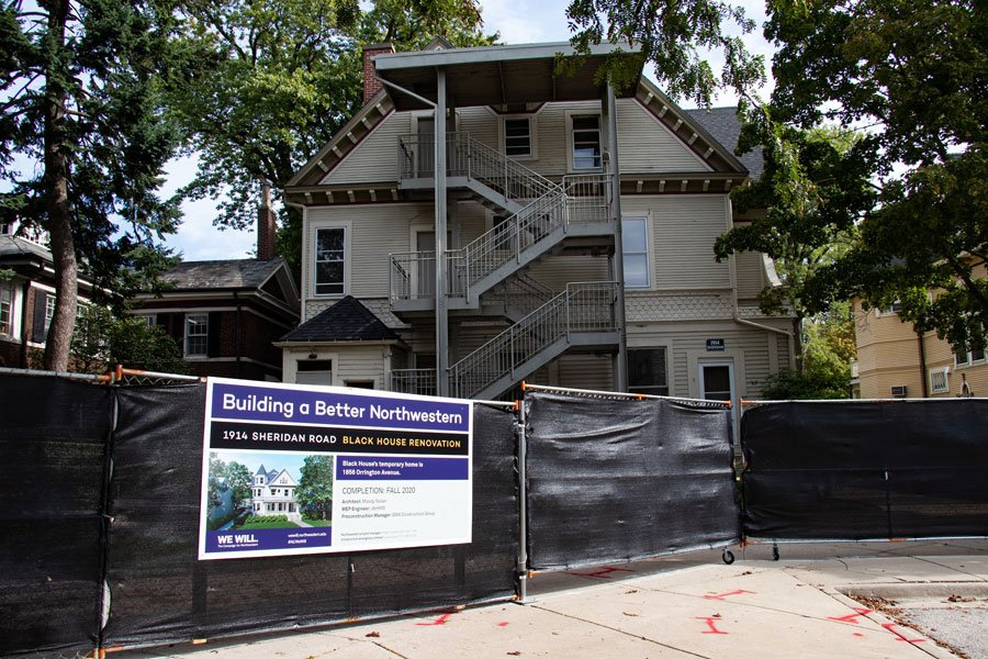 """A building sits behind a black construction tarp fence. A sign on the fence says, """"Building a Better Northwestern. 1914 Sheridan Road. Black House Renovation."""""""