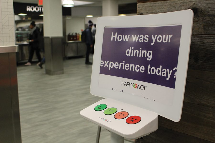"""A sign that says """"How was your dining experience today?"""" with different buttons depicting four different emotions below it. In the background you can see students getting food at a dining hall station."""