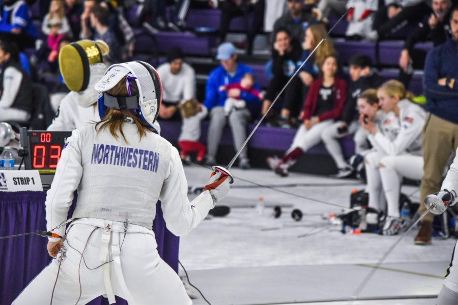 A Northwestern fencer with her sword in the air faces a Notre Dame opponent, off screen except for her sword.